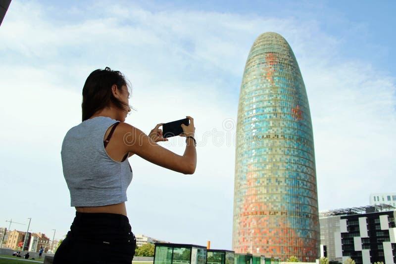 Jeune fille prenant une photo avec le téléphone portable à un bâtiment moderne photos stock