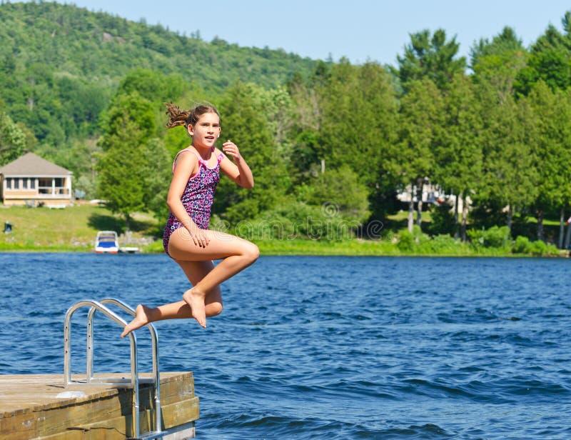 Jeune fille qui s'amuse l'été en sautant dans le lac du quai photo stock