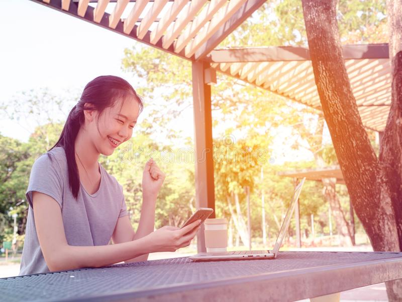 Jeune fille réussie avec un téléphone dans des ses mains travaillant sur un ordinateur portable à la table en parc Le concept des images libres de droits