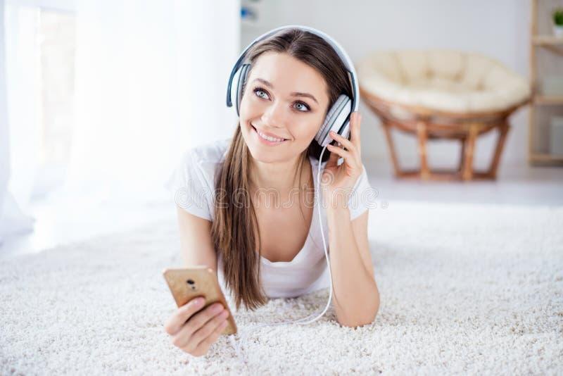 Jeune fille rêvante mignonne écoutant la musique dans le mensonge d'écouteurs photographie stock libre de droits