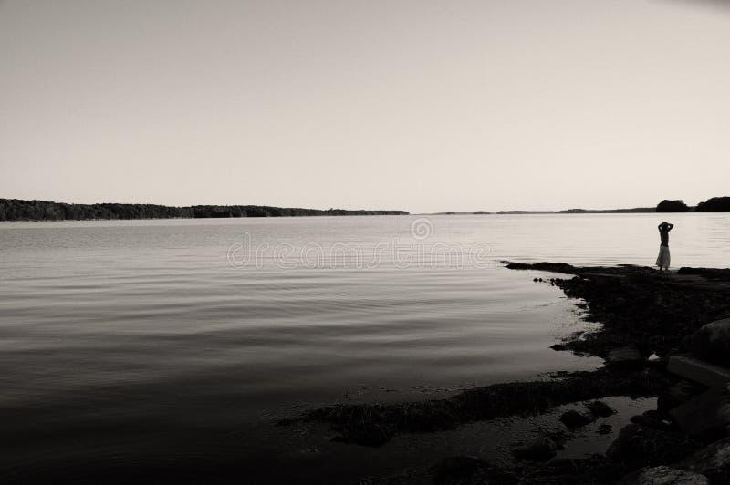 Jeune fille regardant au-dessus de l'eau calme photographie stock