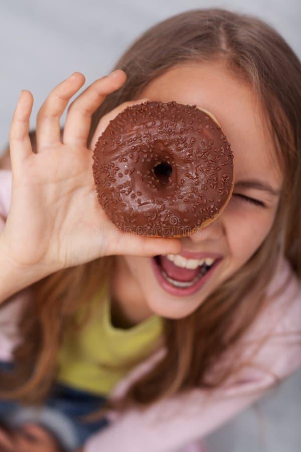 Jeune fille regardant par le trou d'un beignet photos libres de droits
