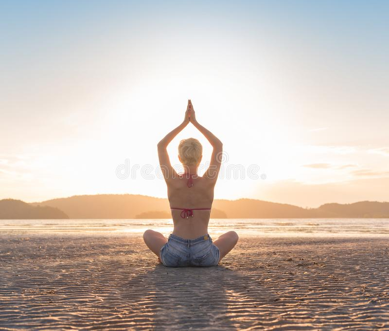Jeune fille reposant le coucher du soleil de Lotus Pose On Beach At, bord de la mer de pratique de méditation de vacances d'été d photos stock
