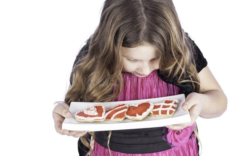 Jeune fille retenant la plaque des biscuits de coeur images libres de droits