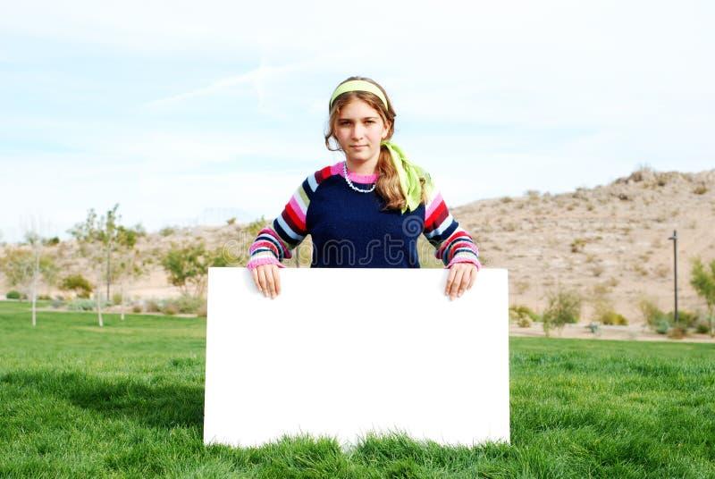 Jeune fille retenant le signe blanc photos stock