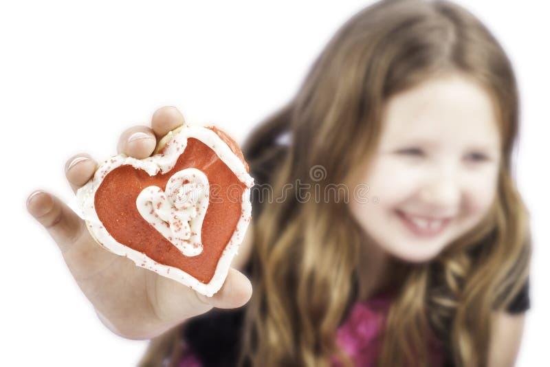 Jeune fille retenant un biscuit de coeur image libre de droits