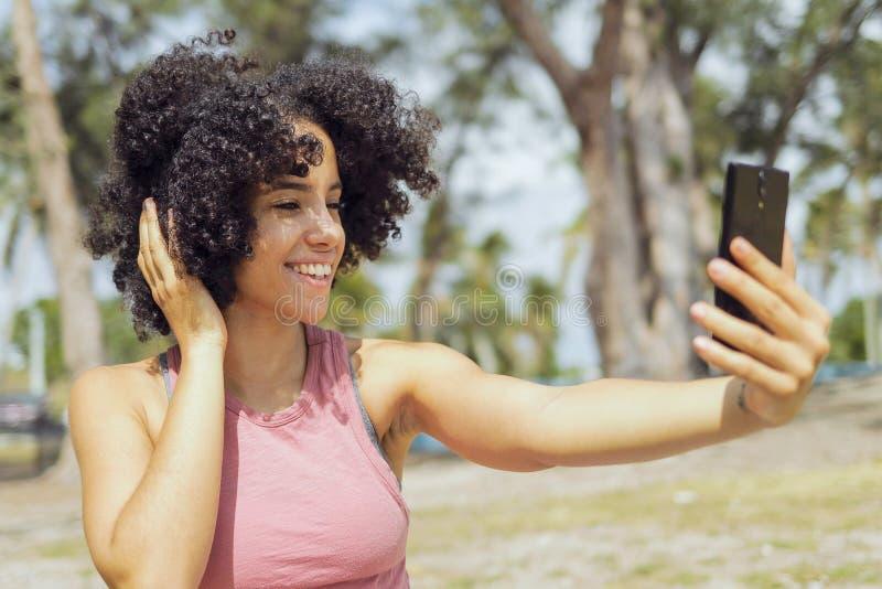 Jeune fille riante prenant le selfie en parc photos libres de droits