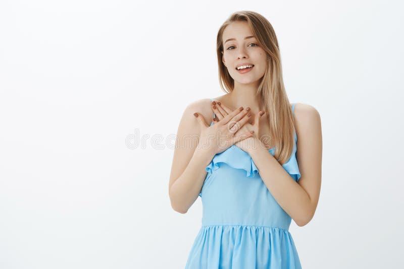 Jeune fille romantique heureuse douce et sincère avec les cheveux blonds dans la robe élégante bleue soupirant de l'amour et de l image stock