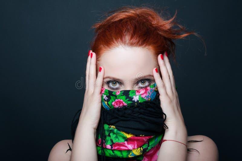 Jeune fille rousse avec l'écharpe florale au-dessus de la bouche images stock