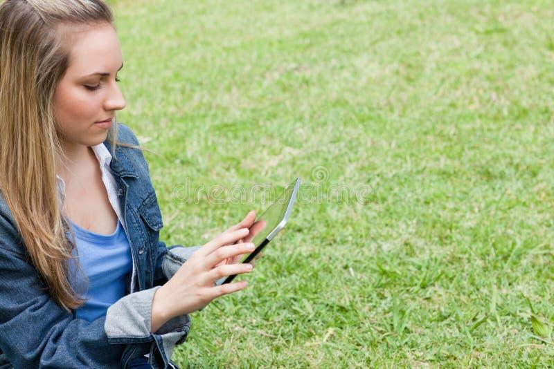 Jeune fille sérieuse à l'aide de son PC de tablette dans le contryside photos libres de droits