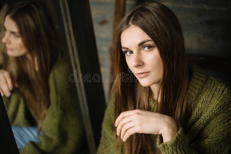 Jeune fille sérieuse dans le chandail confortable tricoté vert-foncé se reposant sur le plancher Portrait en gros plan photos libres de droits
