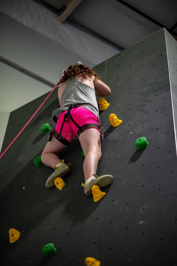 Jeune fille s'élevant sur le mur de pratique dans le gymnase d'intérieur de roche photo libre de droits