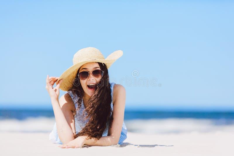 Jeune fille s'étendant sur la plage, souriant photographie stock