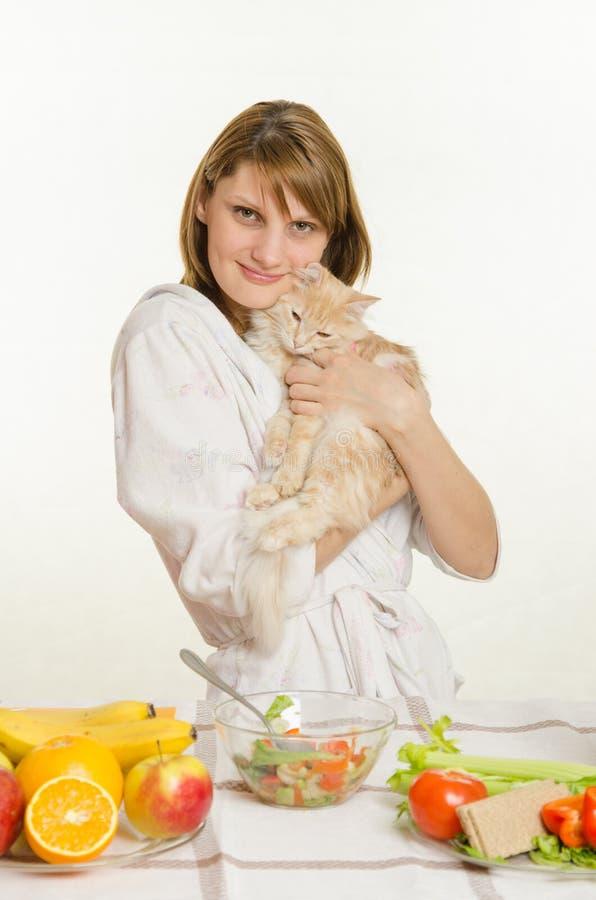 Jeune fille s'asseyant à la table avec les plats végétariens et les prises un chat contrarié images libres de droits