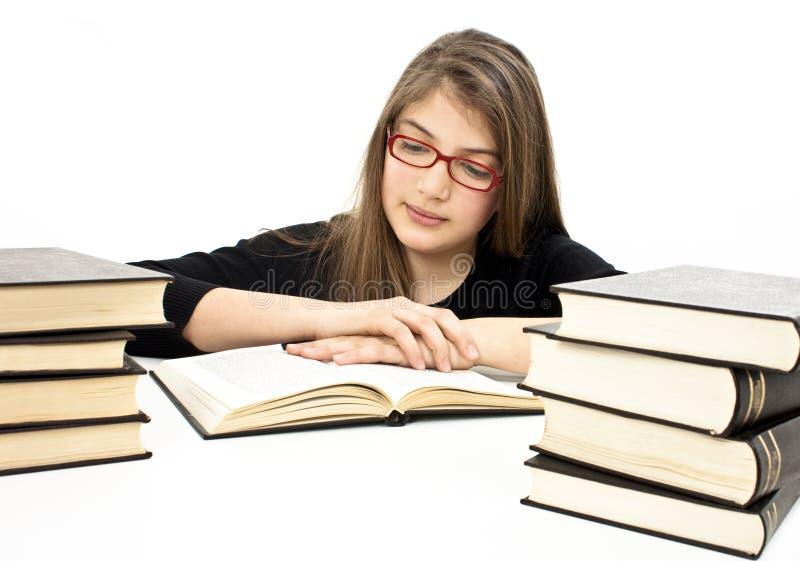 Jeune fille s'asseyant au bureau et au livre de relevé photo stock