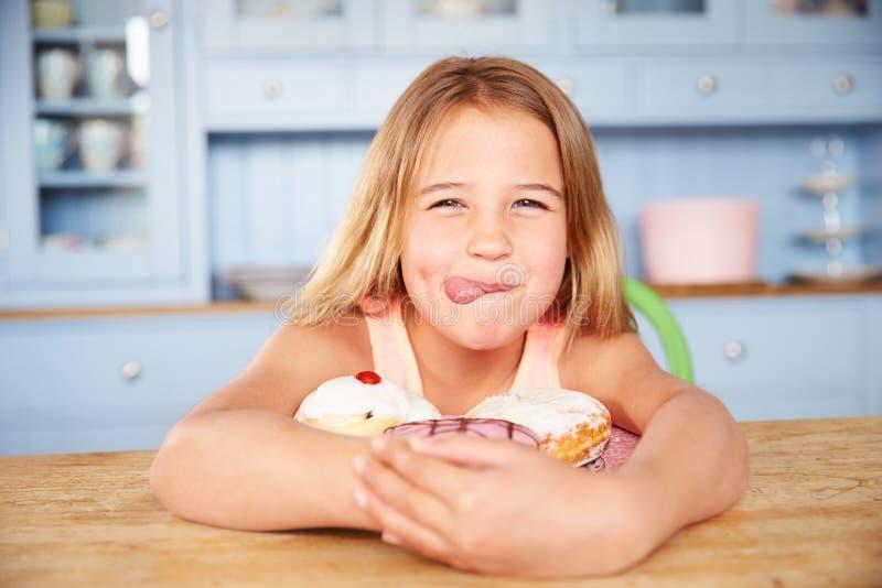 Jeune fille s'asseyant au Tableau regardant le plat des gâteaux sucrés images stock