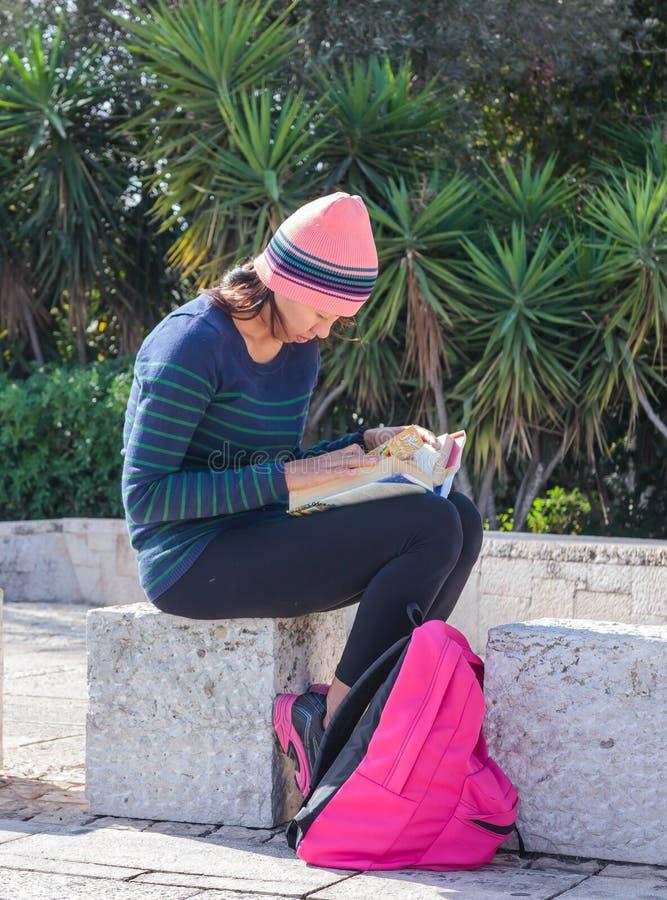 Jeune fille s'asseyant dehors et lisant un livre à Haïfa, Israël image libre de droits