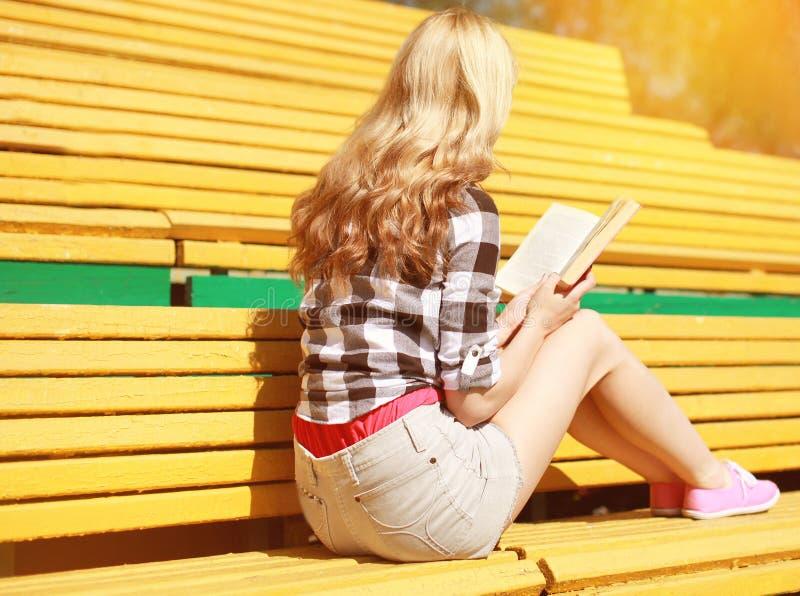 Jeune fille s'asseyant lisant un livre sur le banc photographie stock