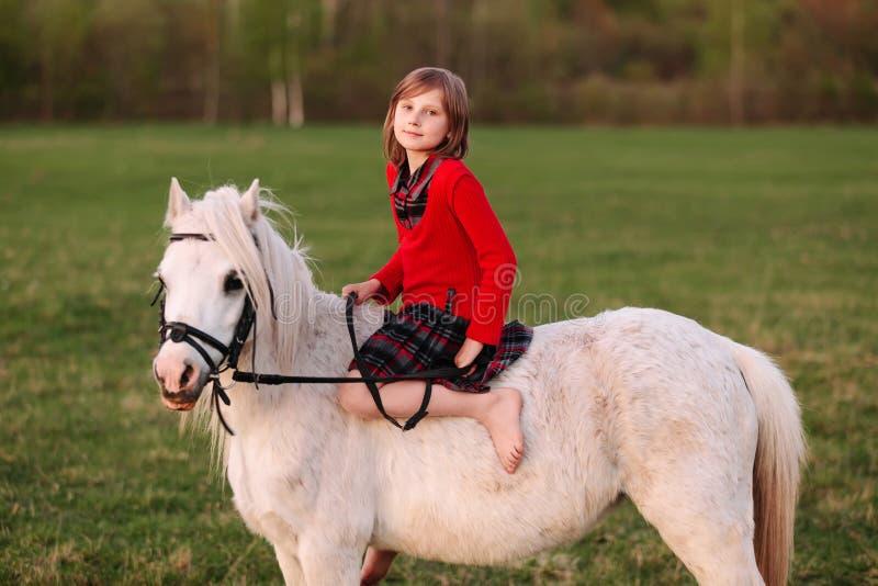 Jeune fille s'asseyant nu-pieds sur un cheval blanc photo libre de droits