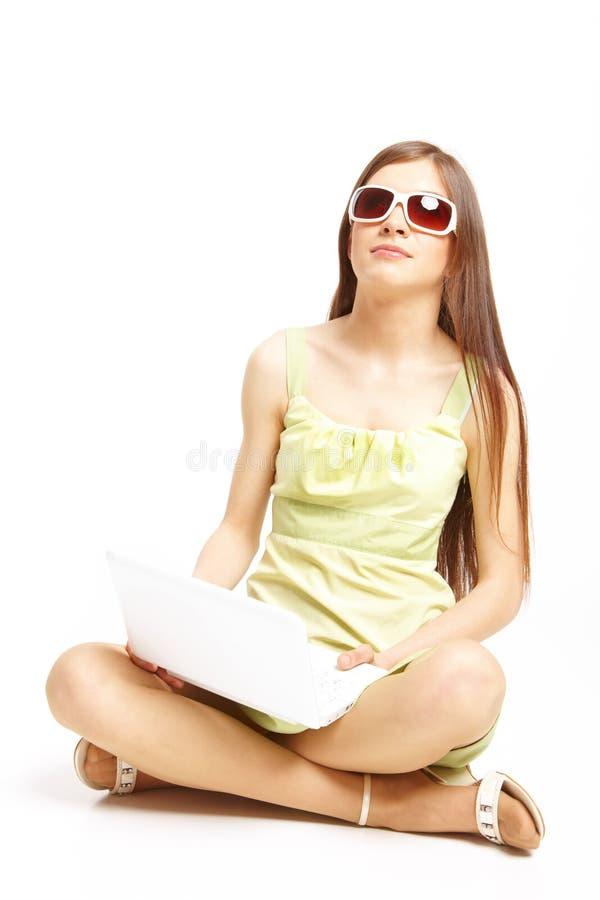 Jeune fille s'asseyant sur l'étage utilisant un ordinateur portatif photos libres de droits