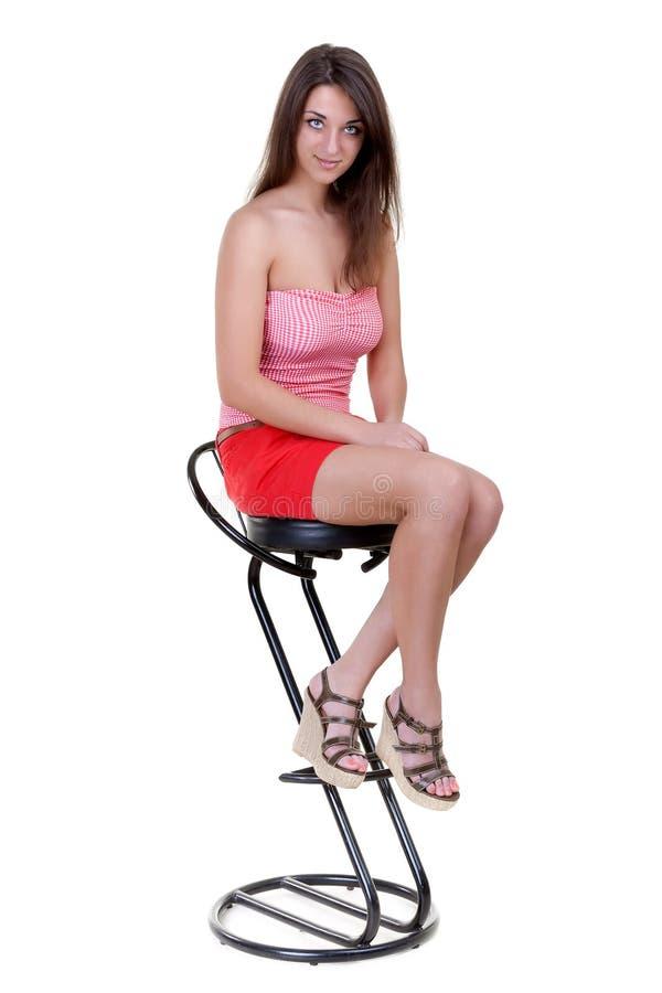 Jeune fille s'asseyant sur un tabouret de bar image libre de droits