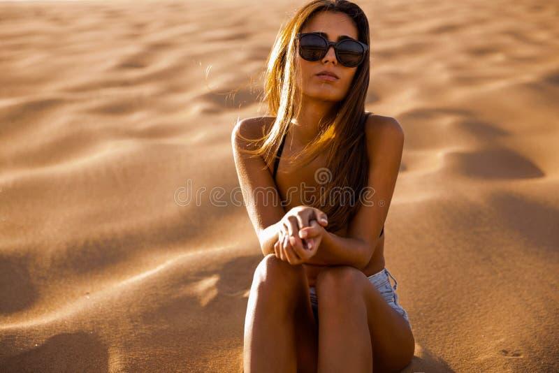 Jeune fille s'asseyant sur une dune de sable photos libres de droits