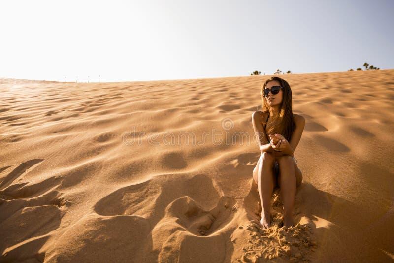 Jeune fille s'asseyant sur une dune de sable image stock