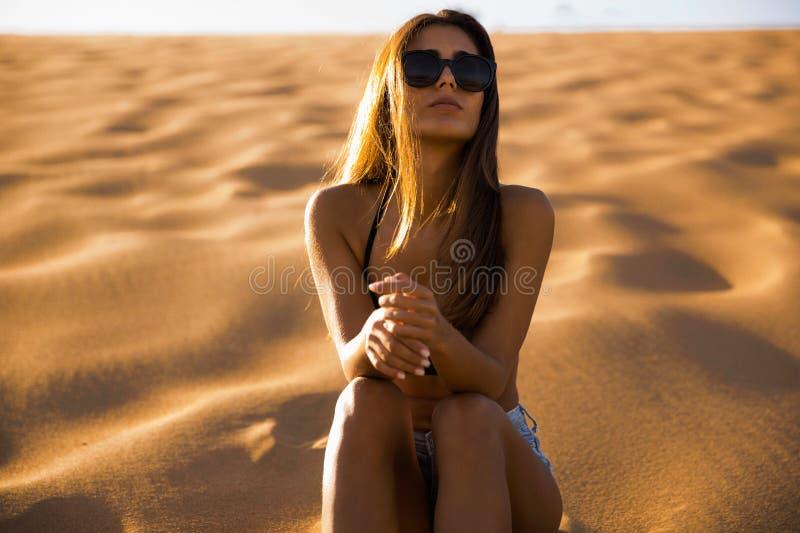 Jeune fille s'asseyant sur une dune de sable photographie stock libre de droits