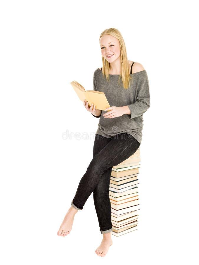 Jeune fille s'asseyant sur une pile des livres photo libre de droits