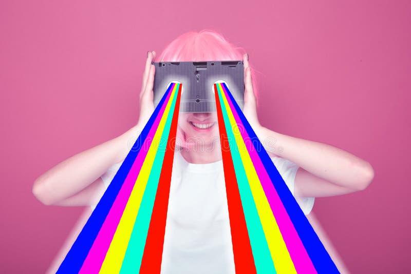 Jeune fille 90s et cassette de VHS sur le rose images libres de droits