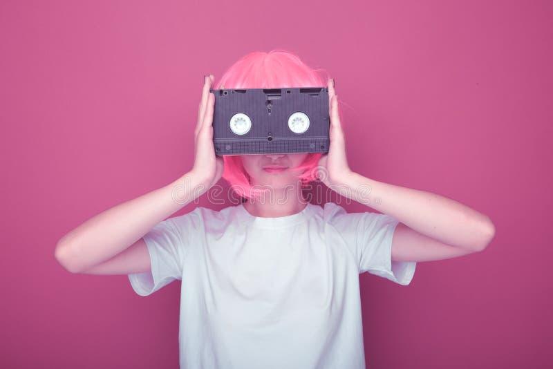 Jeune fille 90s et cassette de VHS sur le rose photos libres de droits