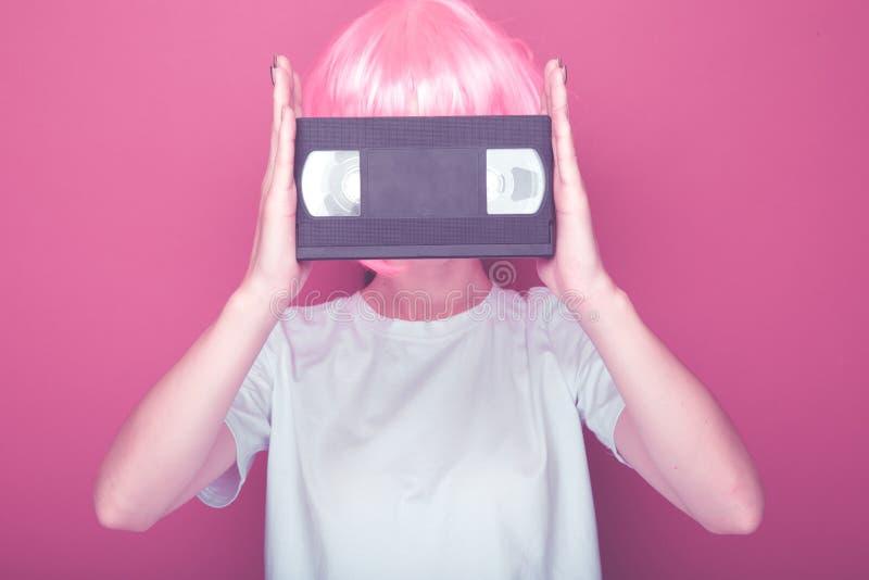 Jeune fille 90s et cassette de VHS sur le rose photos stock