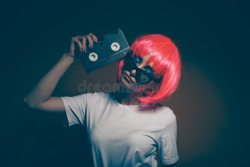 Jeune fille 90s et cassette de VHS sur le rose photographie stock