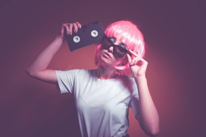 Jeune fille 90s et cassette de VHS sur le rose photo stock