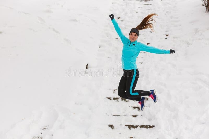 Jeune fille sautant sur la neige photo stock