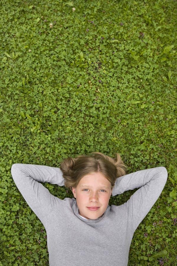 Jeune fille se situant dans l'herbe rêvant de? images stock