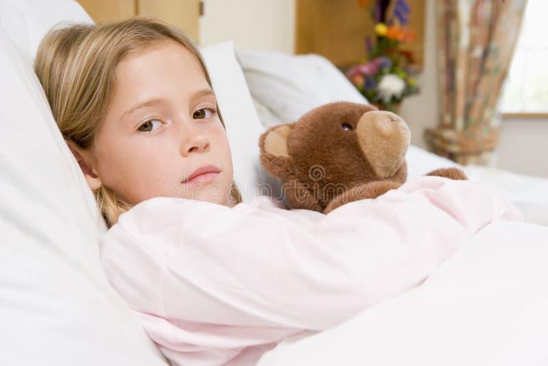Jeune fille se situant dans le bâti d'hôpital avec l'ours de nounours photographie stock