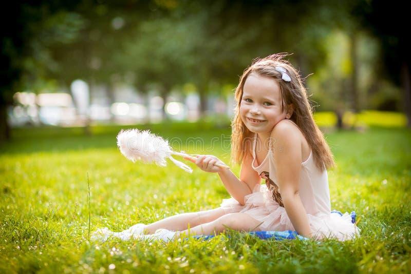 Jeune fille se trouvant sur l'herbe photo stock