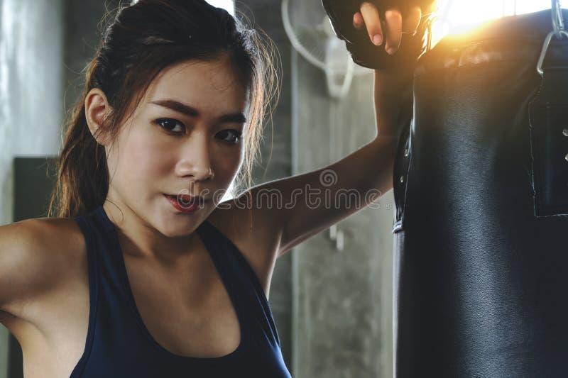 Jeune fille sexy asiatique de combattant poinçonnant activement au gymnase photo libre de droits
