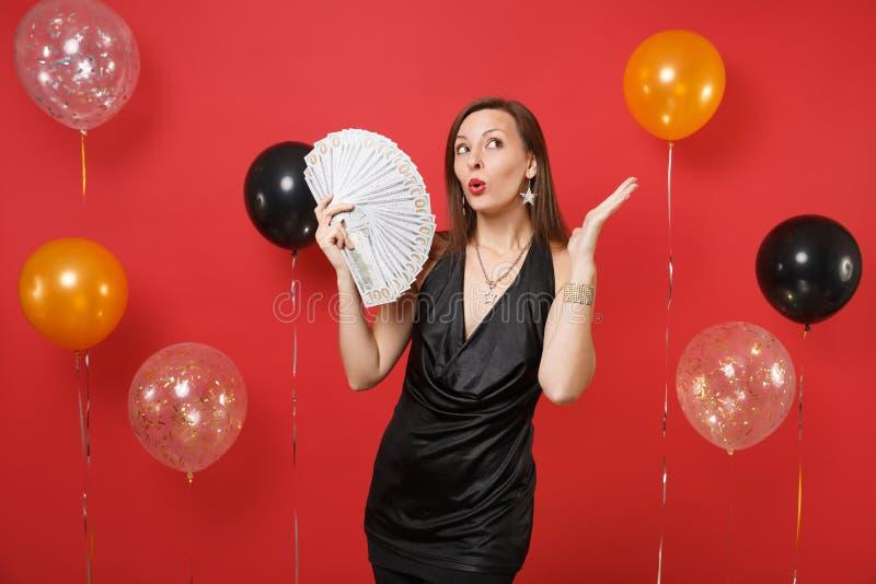 Jeune fille songeuse dans la robe noire recherchant, mains de propagation, tenant un bon nombre de paquet de dollars, argent d'ar photo stock