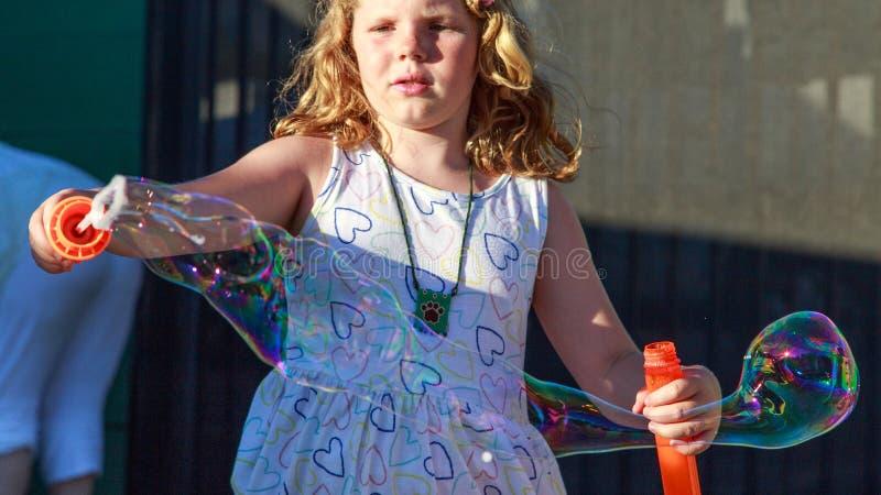 Jeune fille soufflant de grandes bulles photo stock