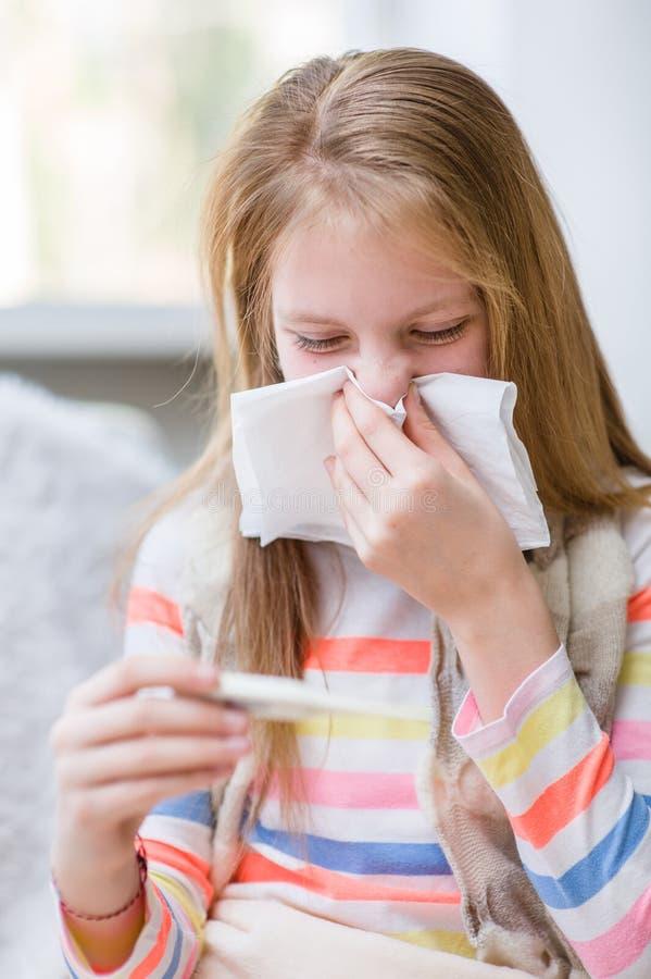 Jeune fille soufflant son nez et contrôles la température image stock