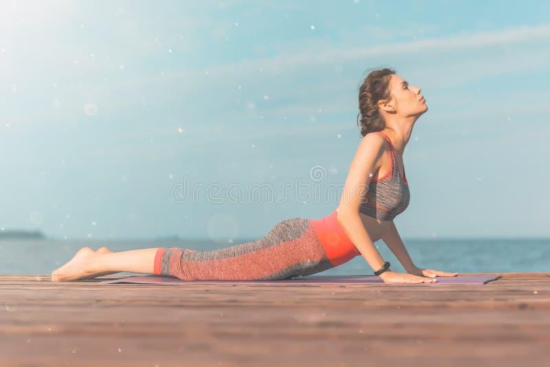 Jeune fille sportive pendant le matin sur le pilier sur le bord de la mer, yoga de pratique La femme font la gymnastique dehors S photographie stock
