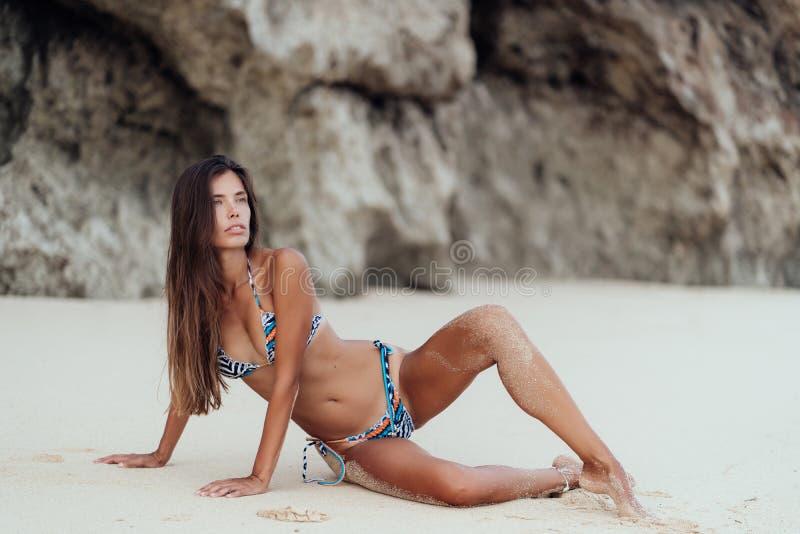 Jeune fille sportive sexy dans des v?tements de bain color?s situant sur la plage blanche de sable images stock
