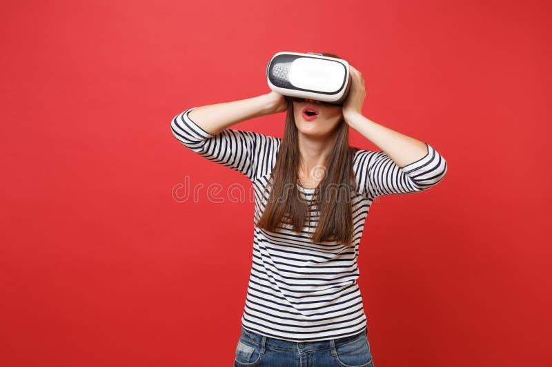 Jeune fille stupéfaite dans des vêtements rayés, verres de réalité virtuelle maintenant la bouche grande ouverte, mettant des mai images libres de droits