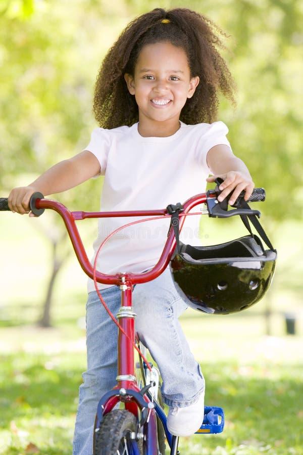 Jeune fille sur la bicyclette souriant à l'extérieur image libre de droits
