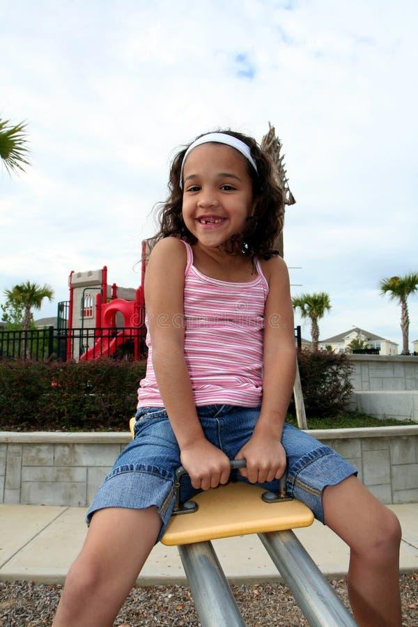 Jeune fille sur la cour de jeu photo stock