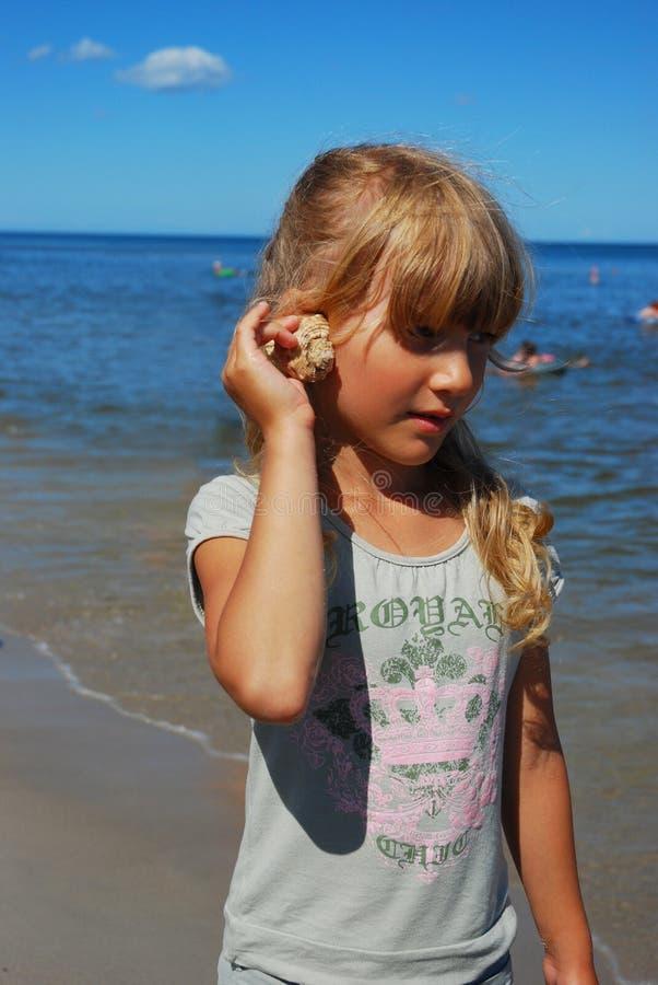Jeune fille sur la plage avec l'interpréteur de commandes interactif photographie stock