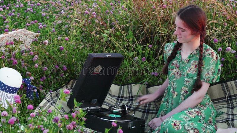 Jeune fille sur le pique-nique dans le pré écoutant le disque sur le phonographe de vintage banque de vidéos