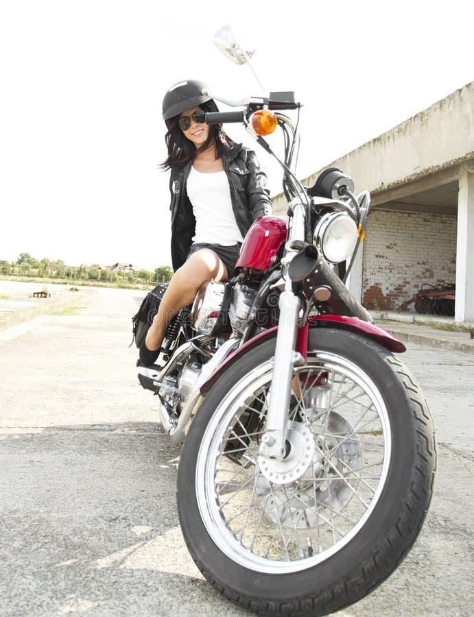 Jeune fille sur une moto photographie stock libre de droits